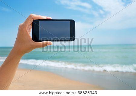 photoshooting on smartphone at sea coast