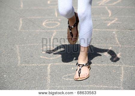 Cute girl playing hopscotch outside