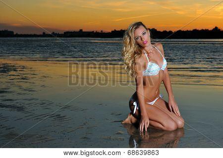 Young woman in bikini on the beach at sunset