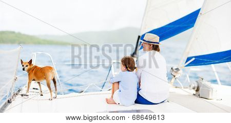 Back view of mother, daughter and their pet dog sailing on a luxury yacht or catamaran boat