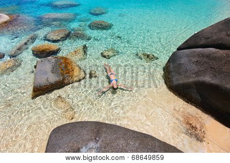 Above view of beautiful young woman relaxing floating in turquoise tropical water among granite boulders at Virgin Gorda, BVI, Caribbean