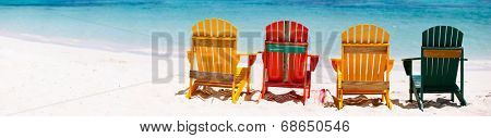 Row of colorful wooden chairs at tropical white sand beach in Caribbean, panorama with copy space perfect for banners
