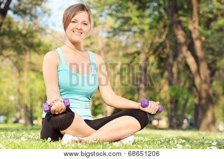 Young female exercising with dumbbells in park seated on grass
