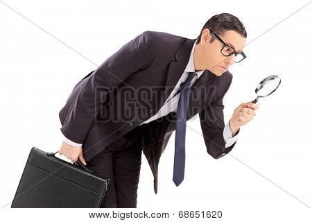 Displeased businessman looking through a magnifying glass isolated against white background