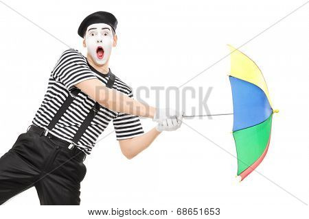 Mime artist holding an umbrella simulating being blown by wind isolated on white background