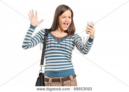 Angry girl looking at a cell phone isolated against white background