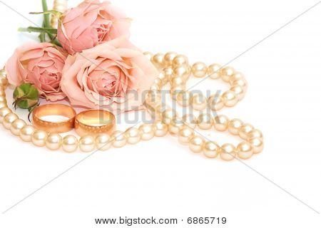 Two Golden Rings, Pearls And Flowers On White Background