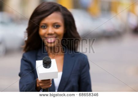 portrait of young african female journalist interviewing people on street
