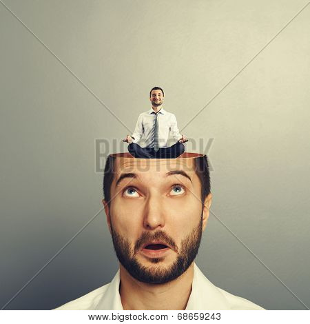 amazed businessman with open head. young calm businessman sitting in yoga asana and smiling in the man's head. photo over grey background