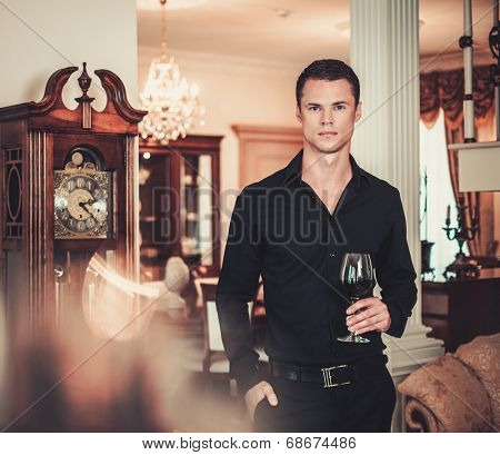 Handsome young well-dressed man in luxury house interior with glass of red wine