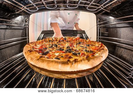 Chef prepares pizza in the oven, view from the inside of the oven. Cooking in the oven.