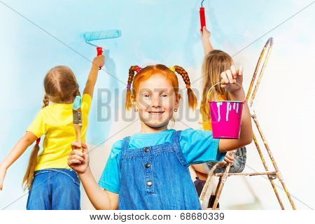 Girl painting wall with friends