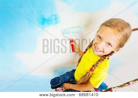 Nice little girl in yellow sits on a ladder