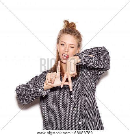 Young Woman Showing La By Finger And Winking