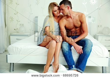 Young couple sitting on the bed a thome
