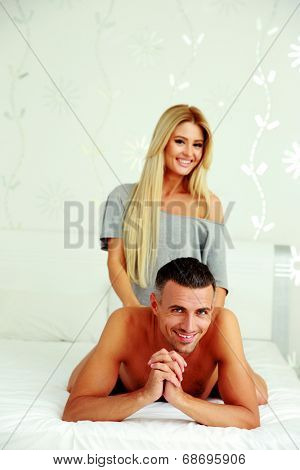 Smiling woman doing a massage to her boyfriend on their bed