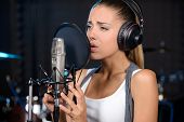 image of recording studio  - Portrait of young woman recording a song in a professional studio - JPG