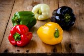 picture of pepper  - Red green black white and yellow bell peppers on wooden background