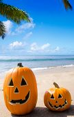 image of rock carving  - Two Halloween pumpkins on the beach by ocean - JPG