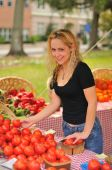 pic of farmers market vegetables  - a young woman selecting tomatoes from a farmer - JPG