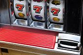 picture of coin slot  - Close up of three seven jackpot on a casino slot machine - JPG
