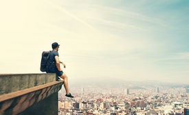 picture of parkour  - Young man is sitting on a roof and looking city - JPG