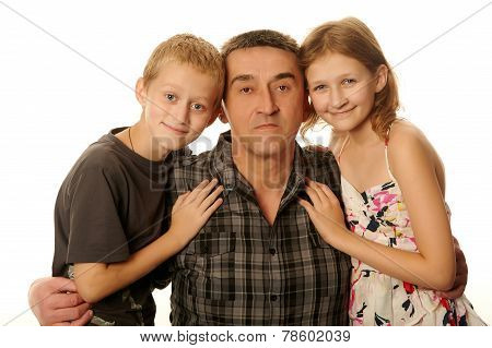 Twelve Year Old Daughter And Ten Year Old Son Having Fun Hugging Father