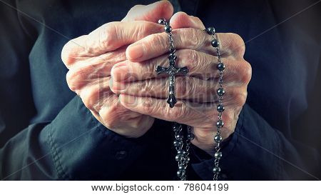 Hands Of An Elder Woman Holding A Rosary While Praying