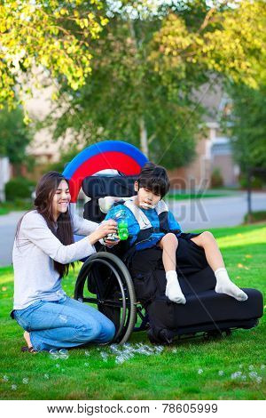 Biracial Older Sister Playing Outdoors With Disabled Little Brother In Wheelchair