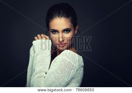 Beautiful Woman In White Sweater Posing In Studio On Dark Background