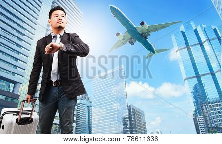 Business Man And Belonging Luggage Watching To Sky And Hand Watch Against High Building Skyscrapers