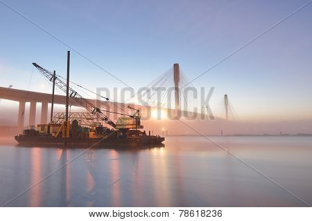 The New Port Mann Bridge and boat lifting crane at sunrise