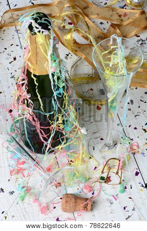 High angle shot of a Champagne bottle, streamers and confetti after a New Years Eve Party. Vertical format with shallow depth of field. Focus is on the foreground and table top.