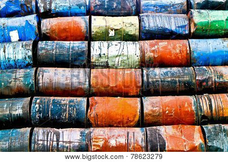 Horizontal staple of colorful used oil drums on a storage site