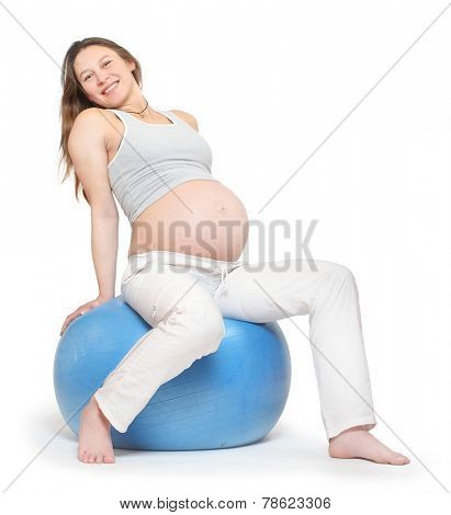 Pregnant woman excercising on blue ball. Prenatal care concept.