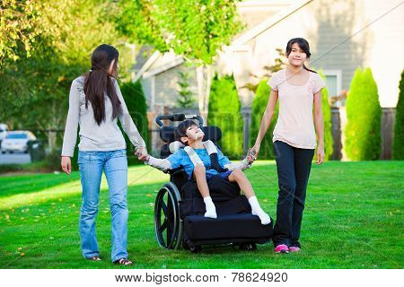 Disabled Little Boy In Wheelchair Walking With Sisters On Glassy Lawn