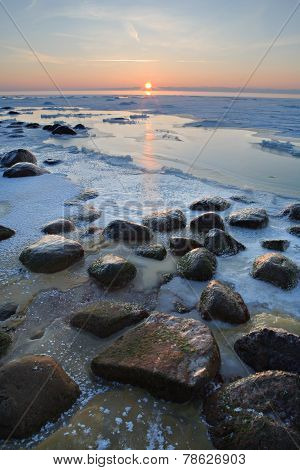 Stones In The Sea Froze In The Ice At Sunset