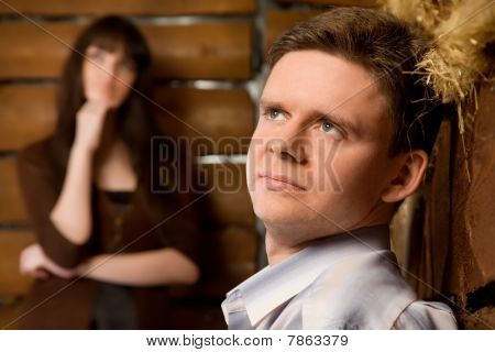 Dreamy Young Man And Young Woman In Wooden Log Hut