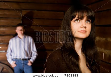 Beautiful Young Woman Brunette And Young Man In Wooden Log Hut