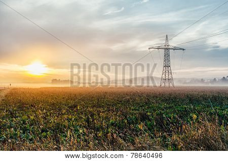 Electric Power Lines And Pylons At Sunset