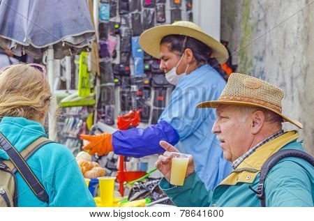 LA PAZ, BOLIVIA, MAY 9, 2014:  Senior tourist drinks freshly squeezed orange juice from a street stand