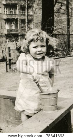 GERMANY, CIRCA 1939 -  Vintage photo of baby girl playing in a sandbox