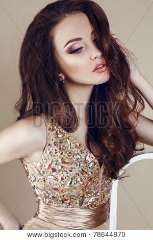 Beautiful Girl With Dark Hair In Sequin Dress Posing At Studio