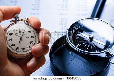 Hand Holding Stopwatch On Budget Numbers