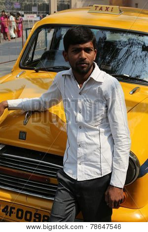 KOLKATA, INDIA - FEBRUARY 14: Indian taxi driver in front of his cab in Kolkata on February 14, 2014. The car is Hindustan Ambassador, manufactured since 1958.