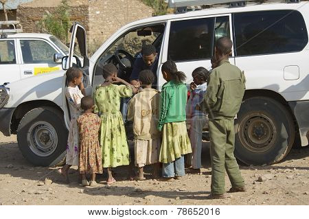 Kids beg for money from a car driver in Adwa, Ethiopia