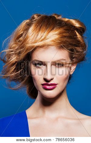 Portrait of lovely young model with beautiful hairstyle. on blue background