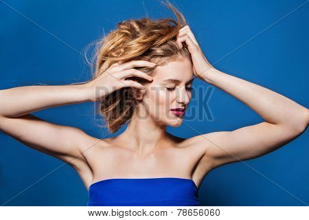 Beautiful woman fashion hairstyle. model with magnificent hair. on blue background