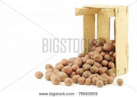 Cherry potatoes (small dutch potatoes) in a wooden crate on a white background