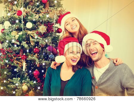 Happy Christmas Family portrait. Smiling Parents with teenage daughter at Home Celebrating New Year. Christmas Tree